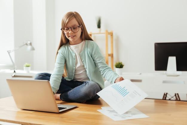 Мотивированный умный классный ребенок работает над своим домашним проектом, изучая некоторые данные
