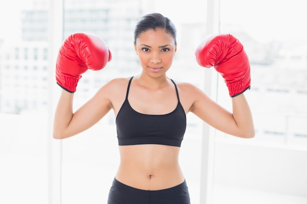 Motivated dark haired model in sportswear wearing red boxing gloves