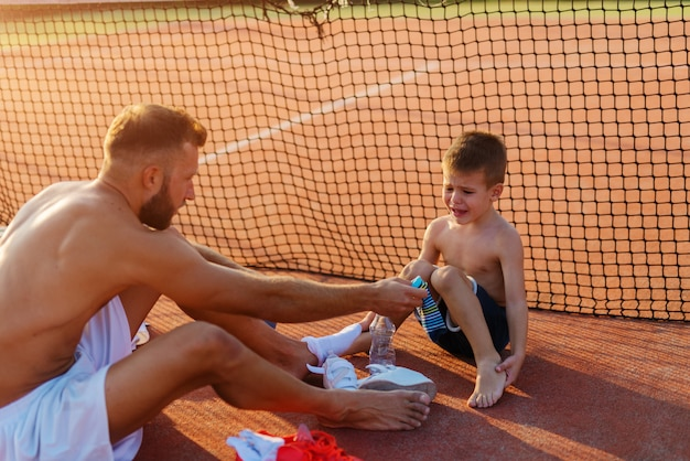 Motivated father trying to convince his son to take his socks on before the training.