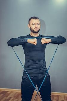 Мотивированный, целеустремленный красивый спортсмен выполняет приседания со скакалкой