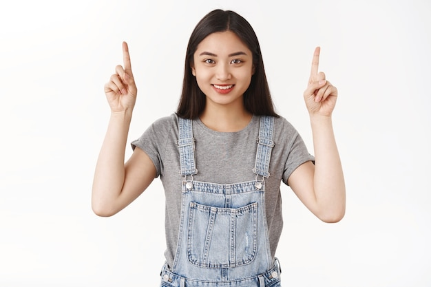 Motivated good-looking confident pleasant happy smiling asian brunette girl aim only forward straight top success pointing up index fingers grin camera delighted propose cool offer promo
