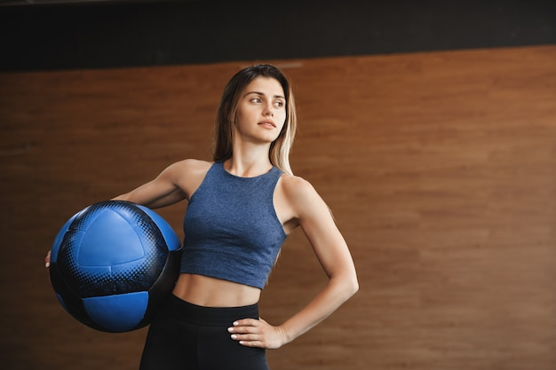 Motivated good-looking sportswoman in sportswear, holding medicine ball on waist and holdinghand on hip.