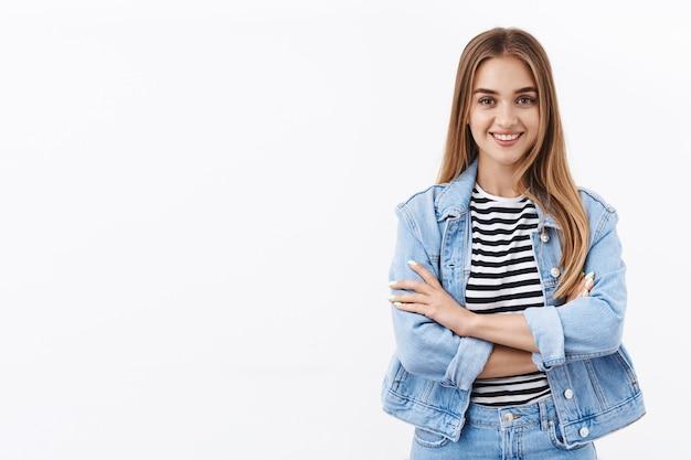 ブロンドの髪、腕を組んで、カメラに向かって笑顔で、夢に向かって行く準備ができて、白い壁に立っている、やる気のある幸せで自信に満ちた若い女性