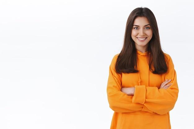 Мотивированная счастливая привлекательная брюнетка в оранжевой хипстерской толстовке с капюшоном, скрестив руки на груди, смотрит в камеру, решительно, готова к действию, стоит у белой стены