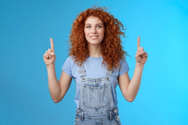 의욕적인 행복한 빨간 머리 어리석은 곱슬머리 여자가 검지손가락을 가리키며 웃고 있는 매력에 매료되어 멋진 프로모션을 보여주며 흥미로운 광고 파란색 배경에 대해 토론합니다.