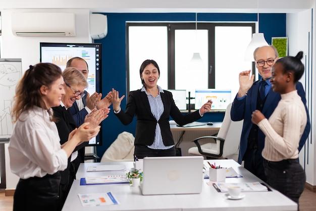 동기 부여된 행복한 다양한 비즈니스 팀 사람들이 기업 회의에서 성공을 축하하는 박수를 쳤습니다. 다민족 파트너 동료들이 회사 브리핑에서 성공적인 팀워크 결과를 축하합니다
