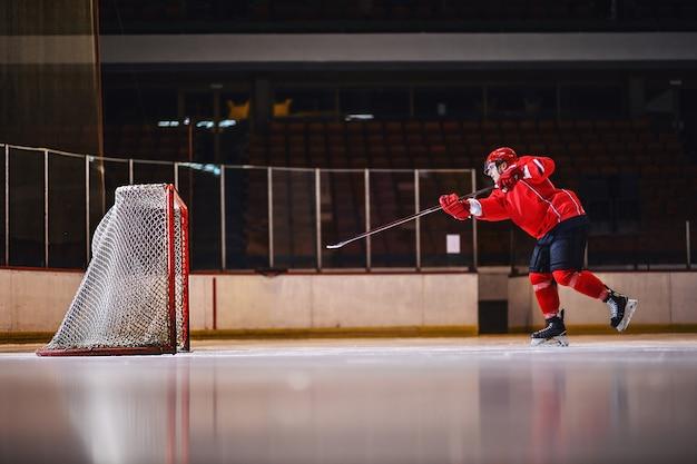 Motivated hockey player training shooting on goal while skating on ice.