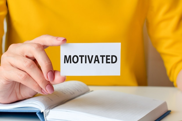 Motivated is written on a white business card. a woman's hand holds a white paper card against the background of a yellow dress and a white notebook. business and advertising concept.