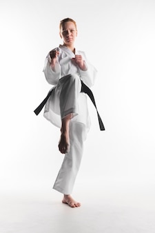 Motivated karate woman kicking front view