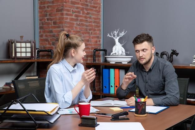 사무실 환경의 회의실 테이블에 앉아 있는 동기 부여된 관리 팀