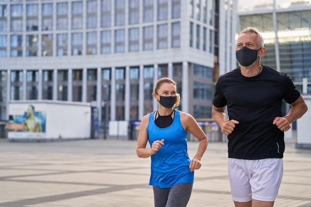 Мотивированная пара среднего возраста женщина и мужчина в защитных масках бегают трусцой на открытом воздухе в городе, чтобы