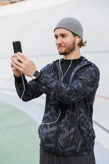 Motivated smiling young fit sportsman listening to music with earphones while standing at the stadium, taking a selfie with mobile phone