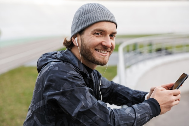 Motivated smiling young fit sportsman listening to music with earphones while standing at the stadium, using mobile phone, leaning on the rail