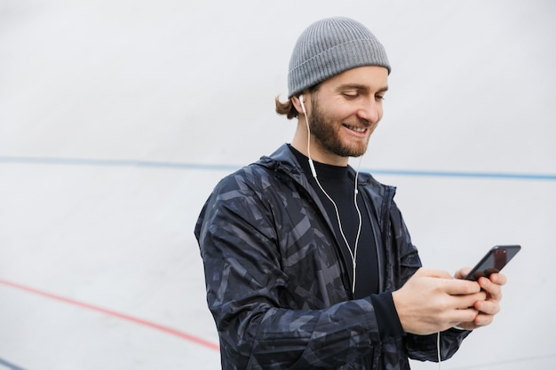 Motivated smiling young fit sportsman listening to music with earphones while standing at the stadium, using mobile phone