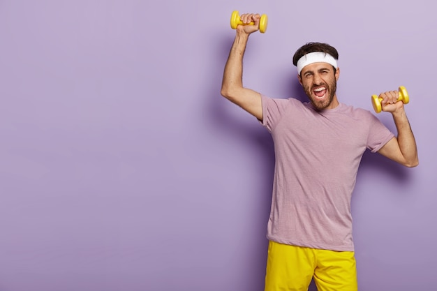 Motivated sportsman trains muscles, raises yellow dumbells, wears headband, casual outfit, being active