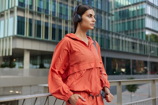 Motivated sportswoman looks with determined expression enjoys workout outdoors has morning exercising routine dressed in activewear listens music poses in downtown. active lifestyle concept