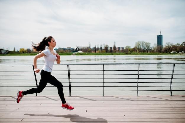 Motivated sportswoman running near the river.