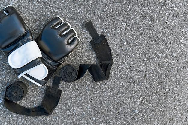싸울 동기 부여. 아스팔트 배경에서 권투 붕대가 있는 스포츠 권투 장갑의 클로즈업