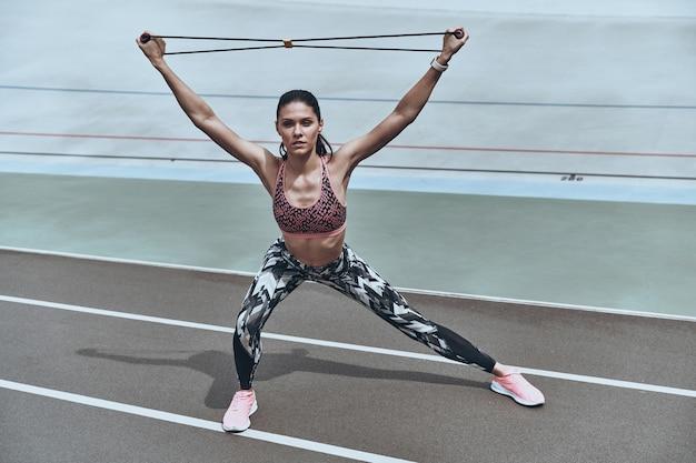 Мотивировано формировать свое тело. красивая молодая женщина в спортивной одежде