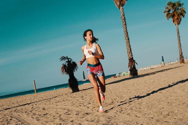 彼女の体を形作ることに動機づけられた。屋外で運動しながらジョギングスポーツ服の美しい若い女性の全長