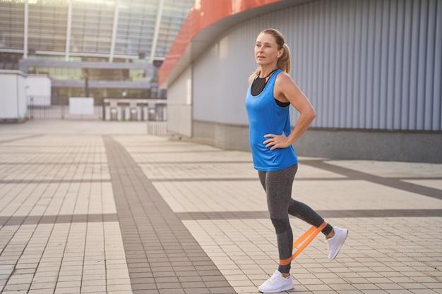 で屋外でトレーニングしながら抵抗バンドを使用して彼女の足を伸ばすスポーツウェアのやる気のある女性