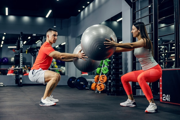 A motivated woman and a man in sportswear do deep squats while holding a pilates ball in their hands