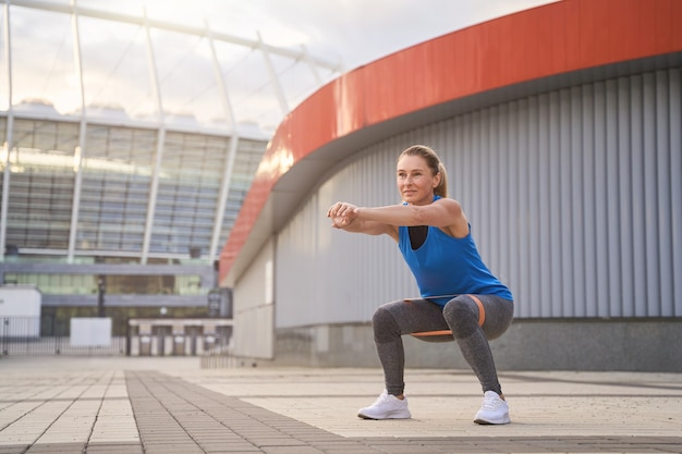 Motivated woman in sportswear doing squats with resistance band while training outdoors in the city