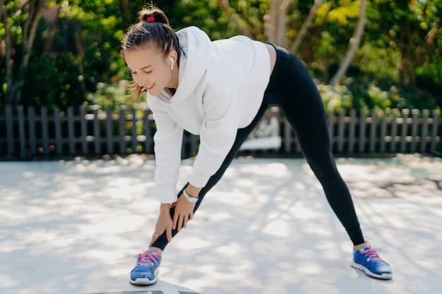 やる気のある若い成人女性が定期的にスポーツに参加し、手から足に寄りかかって身を乗り出し、足を肩幅に広げてスポーツウェアを着用し、減量のための屋外スポーツ活動のトレーニングを楽しんでいます