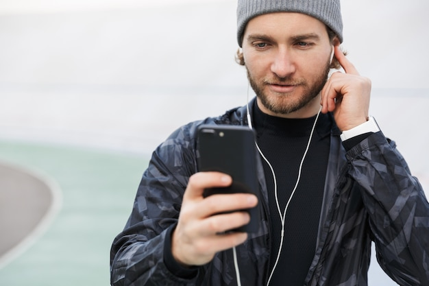 Motivated young fit sportsman listening to music with earphones while standing at the stadium, using mobile phone