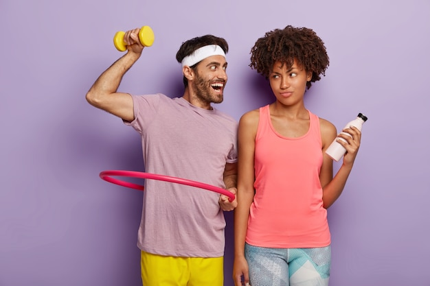 Motivated young man exercises with hula hoop, raises dumbbell, has glad expression, wears white headband and t shirt and displeased woman stands with bottle of water, has fitness training