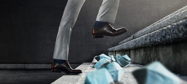 Motivation and leadership concept. businessman step up on staircase to pass through many used medical mask. start for new challenge. metaphor photo