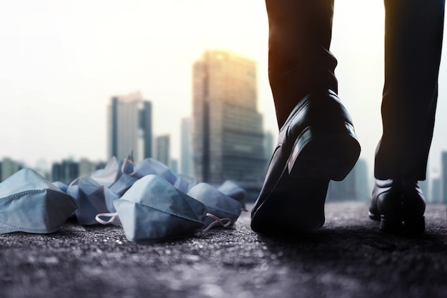 モチベーション、成功するコンセプトへの一歩。コロナウイルス中のビジネスへの挑戦。地上で医療マスクを通過するために前に歩いているビジネスマンの低いセクション