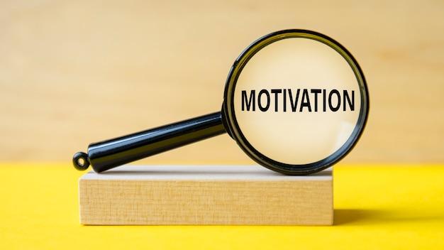 Слово мотивации через увеличительное стекло на деревянных фоне. увеличительное стекло закреплено на деревянной подставке на желтом столе