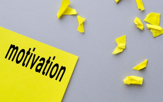 Motivation a word written on yellow paper, next to torn shreds on a gray table, the concept of success.