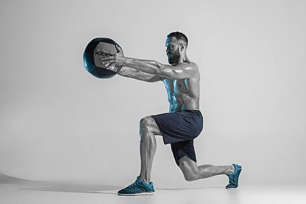 자극. 네온 불빛에 스튜디오 배경 위에 젊은 백인 보디 빌딩 훈련. 공 근육 질의 남성 모델입니다. 스포츠, 보디 빌딩, 건강한 라이프 스타일, 동작 및 행동의 개념.