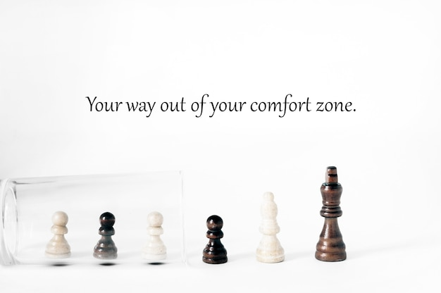 Motivational concept,  getting out of the comfort zone. a row of chess pieces comes out of a glass cup.