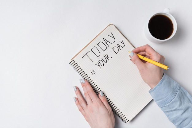Motivational inscription today is your day. top view of woman writing in notepad. morning coffee