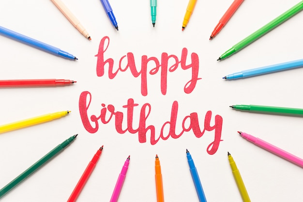 Мотивационная фраза «с днем рождения» для поздравительных открыток и плакатов, рисование красным маркером на белой бумаге. надпись на бумаге между красочными маркерами