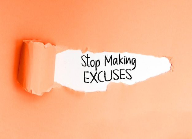 Motivational phrase stop making excuses, written on a torn paper