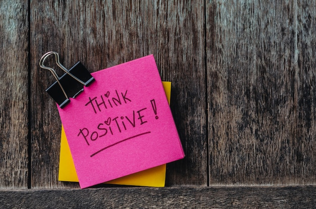 Motivational think positive slogan note pads and paper clip on old wood background