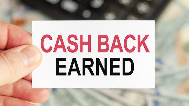 동기 부여 단어 : 캐쉬백 획득. 남자는 텍스트가있는 종이를 들고 있습니다. 비즈니스 및 금융 개념