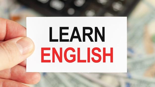 やる気を起こさせる言葉:社債。男はテキストで一枚の紙を持っています:英語を学びます。ビジネスと金融の概念