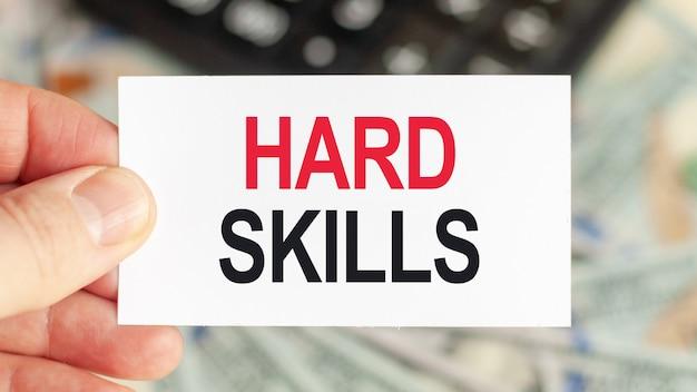 동기 부여 단어 : 어려운 기술. 남자는 텍스트가있는 종이를 들고있다 : hard skills. 비즈니스 및 금융 개념