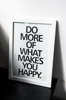 The motivational words do more of what makes you happy on photo frame near the white wall