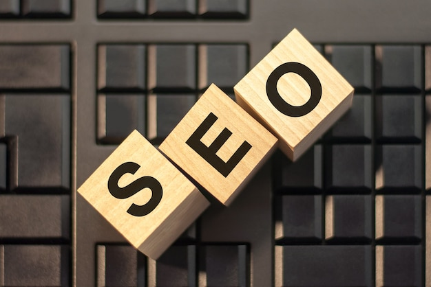 Motivational words: seo in 3d wooden alphabet letters on a keyboard background with copy space, business concept. ceo - short for search engine optimization.