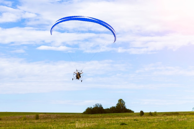 Moto paraglider flying over a field in a blue sky with clouds.