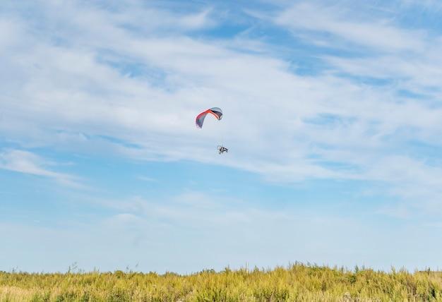 青い空と緑の草の上のモトパラグライダー。