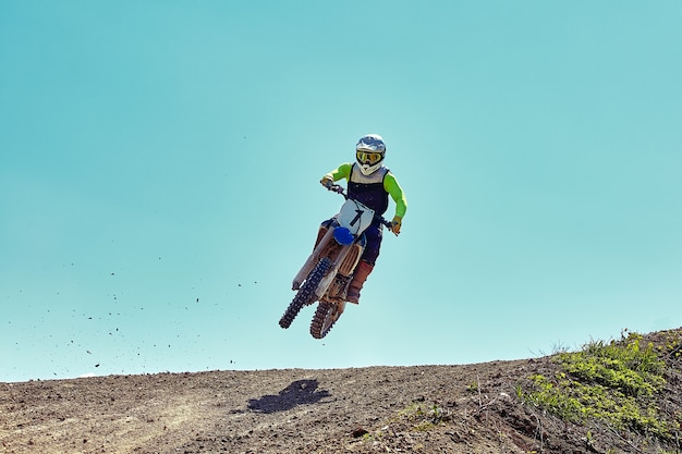 Motocross concept, biker goes off-road making extreme skiing.