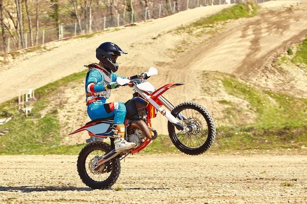 バイクを加速するモトクロスドライバーが離陸し、レーストラックのスプリングボードにジャンプします。