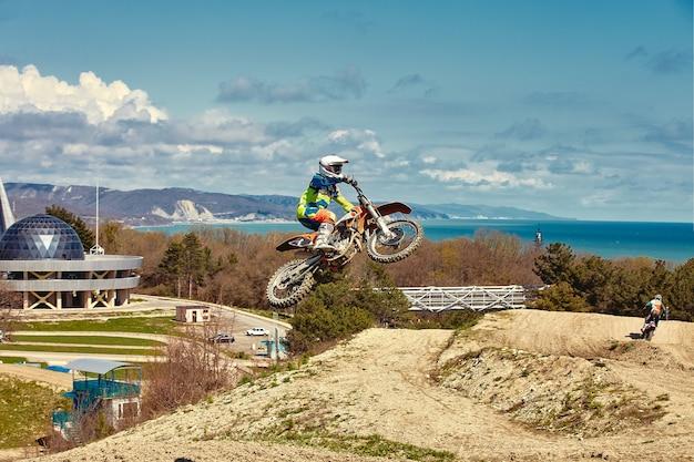 バイクを加速するモトクロスドライバーが離陸し、レーストラックのスプリングボードにジャンプします